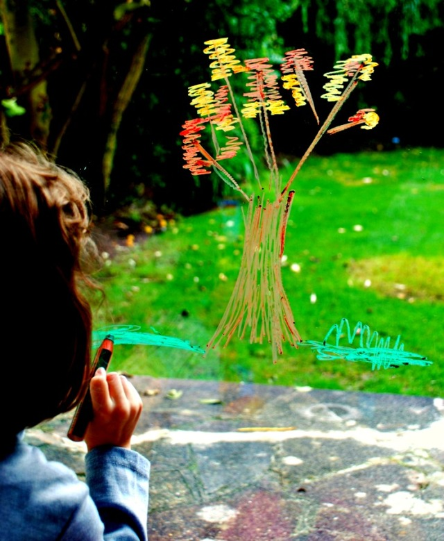 Autumn art activity for kids. Drawing an autumn tree on the sliding doors at home