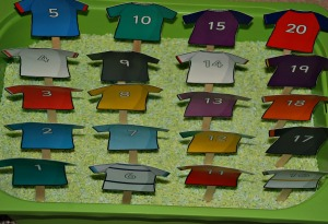 Numbered Rubgy Tops on craft sticks in some green rice on ofamilyblog