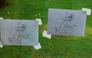 Tape the pictures onto the outside window or sliding door using masking tape