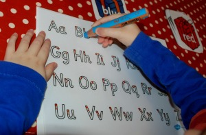 Using his letter tracing sheet to spell out words