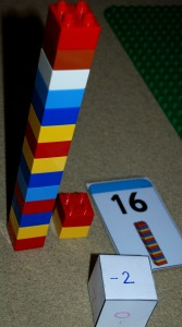 Lego cards and simple dice used to work out a simple subtraction sum on ofamilyblog