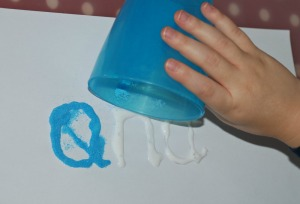 sand words - using a cup to sprinkle the sand onto the glue