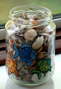 Decorated glass jars using the Rainbow Fish images from the Twinkl website