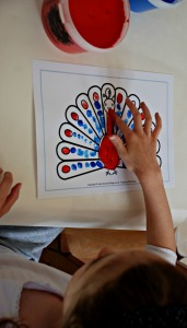 Finger painting on a peacock colouring page from Activity village
