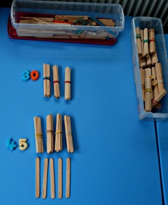 Magnetic numbers and craft sticks to work out tens and ones on ofamilyblog