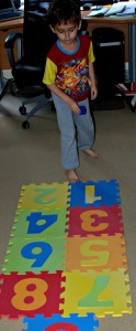 Throwing his dice onto the foam hop scotch mat