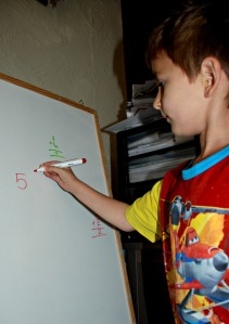 Writing his sums out on the white board