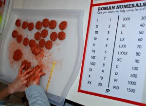 Making clay Roman coins. Using air drying clay and a Roman Numeral poster