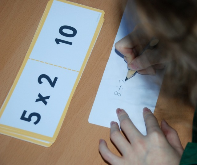 Writing out the division sums on the reverse side of her multiplication cards