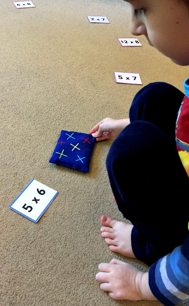 Times table practice with Twinkl's folding cards and some bean bags