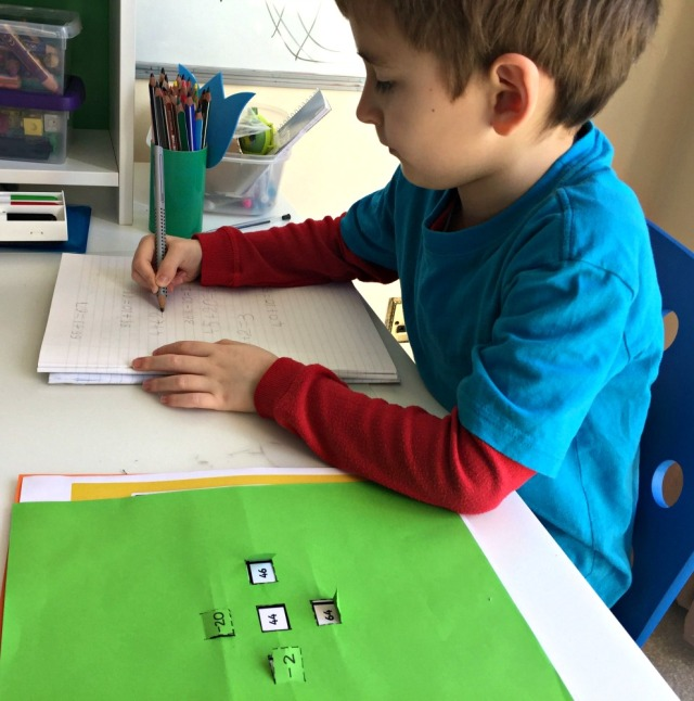 Working out his own sums using a 100 square and a home-made number flap