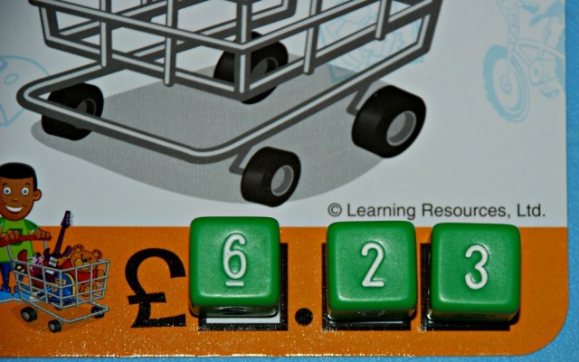 Buy It Right game from Learning resources. The bottom of the shopping cart has three spaces for the dice to go which represent the amount an item costs