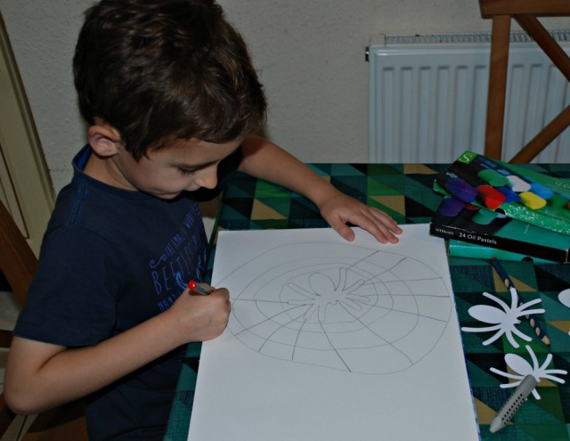 Drawing his spider picture using the spider templates from Activity Village