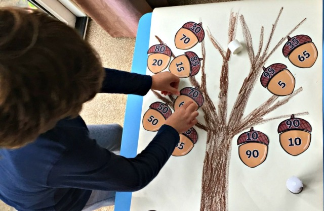 Creating an acorn tree at home. Each acorn needs to add up to 100. Acorns from the Twinkl Resources website