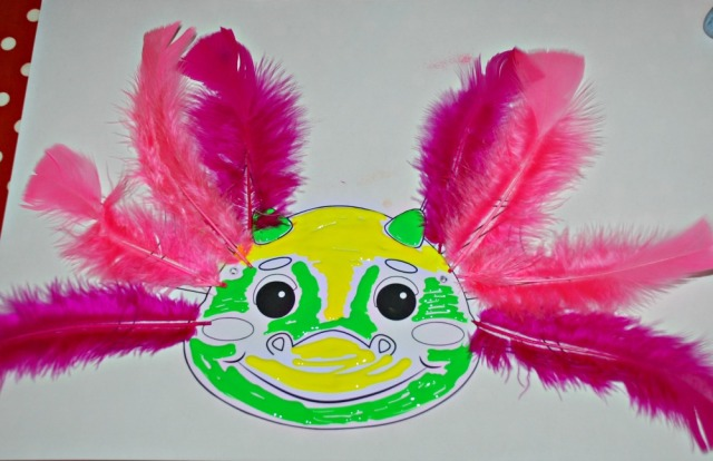 Dragon mask from Activity Village decorated with paints and feathers