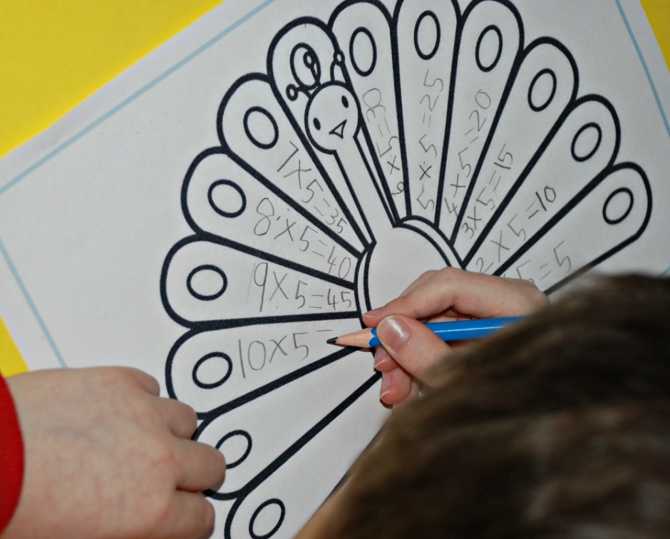 Writing out his 5 times table sums on the feathers of a peacock from the activity village website