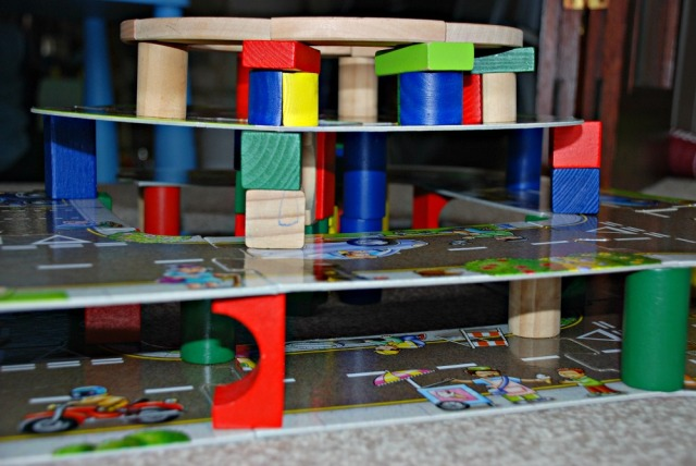 building multi-leveled road structures using his giant road puzzle and some wooden blocks