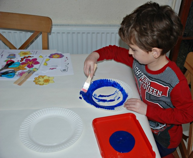 Painting cut out paper plates for the flower wreaths