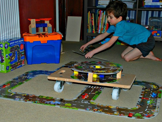Using his giant road floor puzzles to build creative roads