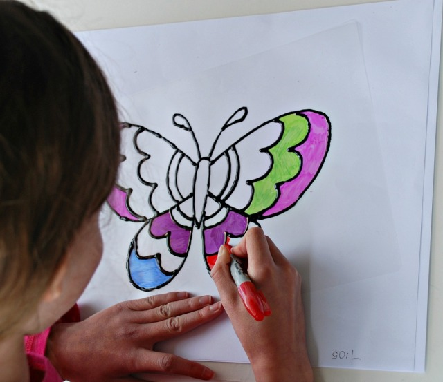 Colouring in our home-made butterfly suncatchers with sharpies