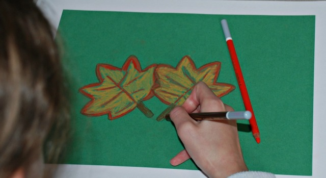 Using her chalk pastels to create some Autumn leaves