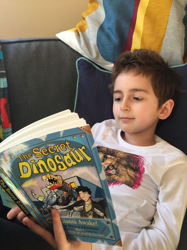 reading The Secret Dinosaur Giants Awake book. The Dinotek Adventure Book 1. A fun early chapter book about metal dinosaurs